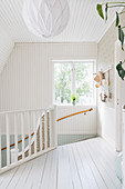 Bright, Scandinavian-style stairwell and landing with board floor
