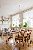 Chairs with turned legs and spindles around table in country-house-style dining room