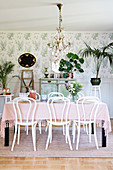 Bistro chairs around set table in classic, feminine dining room
