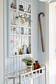 Vintage-style ornaments on narrow shelves mounted on pale blue board wall in hallway