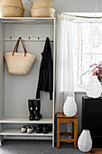 Baskets, row of pegs and shoe rack in grey cloakroom