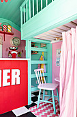 Counter and seating area below loft level in play house in American fifties style