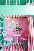 Zwei Stühle und Tisch vor pinkfarbener Wand, darüber Hochbett im Spielhaus