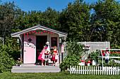 Spielhaus in amerikanischem Fifties-Style und spielende Kinder im Garten