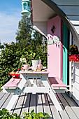 Tisch mit Sitzbank auf der Terrasse des Spielhauses in amerikanischem Fifties-Style