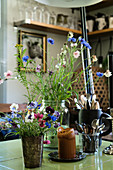 Vase of cornflowers and vintage accessories on kitchen table