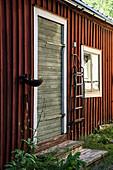 Anbau mit rotbraunem Anstrich und Holztür