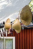 Straw hats hung from bunting below awning