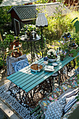 Vintage-style garden furniture, plants on table and standard lamp on summery wooden terrace