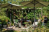 Shady spot below parasols on wooden terrace in summery garden