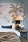 Double bed with headboard and bedside table against large art print