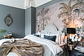 Double bed with headboard and bedside table against large art print in bedroom with grey walls