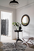 Antique table, upholstered stool, zebra-skin rug and round mirror