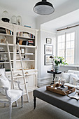 Armchair in front of bookcase with library ladder and ottoman in living room