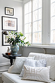 Polstersofa mit Kissen und Antik Beistelltisch mit Lilien vor Sprossenfenster