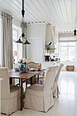Loose-covered chairs and armchair in dining area with white wooden floor