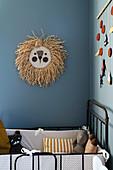 Raffia lion head on blue-grey wall above cot in nursery