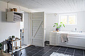 Open barn-style door in low-ceilinged bathroom