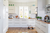 Bright, white, spacious kitchen with wooden floor