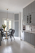 Black rattan chairs around round table in grey kitchen-dining room
