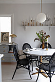 Black rattan chairs around round table in classic dining room