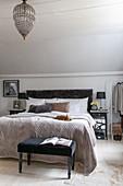 Polsterbank am Bett im Schlafzimmer in gedeckten Farben