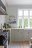 Traditional wood-fired cooker and panelled cabinets in classic kitchen