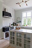 Glass-fronted cabinet in classic country-house kitchen with wood-fired cooker