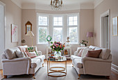 Two sofas facing one another in elegant living room with bay window