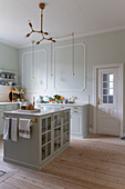 Glass-fronted cabinet in classic country-house kitchen with pale green walls