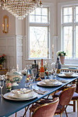 Festively set blue dining table in glamorous dining room