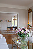 Vase of flowers on coffee table and view into elegant dining room