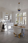 Vintage-style, free-standing bathtub in white, spacious bathroom