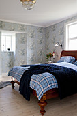 Antique wooden bed in bedroom with vintage-style floral wallpaper