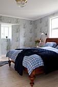 Antikes Holzbett in Schlafzimmer mit nostalgischer Blumenmustertapete