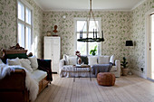 Loose-covered couch, antique wooden sofa and green-and-white floral wallpaper in eclectic interior