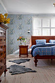 Antique wooden bed, bedside cabinet and vintage-style floral wallpaper in bedroom