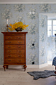 Antique tallboy in bedroom with vintage-style, pale blue, floral wallpaper