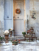 Front door surrounded by wintry decorations dusted with snow