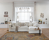 Pale sofa in front of bay window in rustic living room