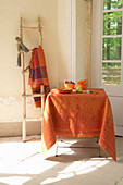 Orange tablecloth and late-summer decorations on table