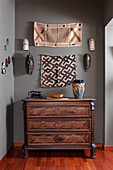 Carved walnut chest of drawers in hallway with grey walls