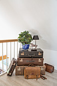 Decorative storage in stack of old suitcases and leather bags