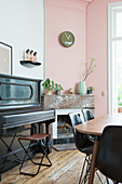 Piano next to open fireplace in dining room with pink wall
