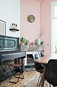 Klavier neben dem offenen Kamin im Esszimmer mit rosa Wand