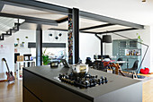 Kitchen island in open-plan loft apartment with steel joists