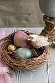 Nest mit bunten Eiern und goldfarbenem Vogel als Osterdekoration