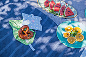 Pretzel on hand-sewn picnic bag and plates of sliced oranges and watermelons