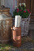 Newspaper holder made from rusty old milk churn