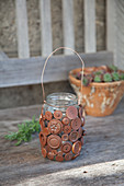 Candle lantern made from screw-top jar and buttons painted rust-red